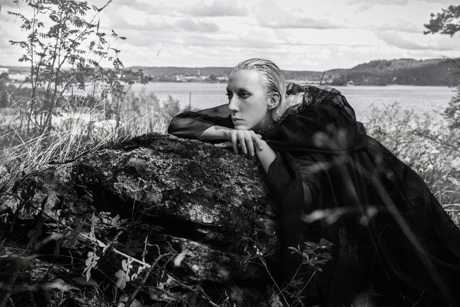 Блондинка в чёрном плаще лежит на черном камне в лесу