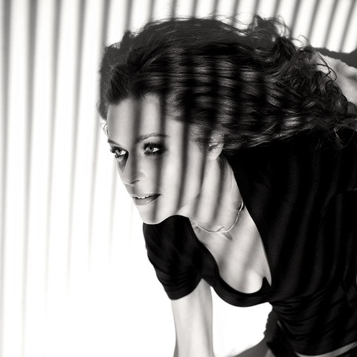 молодая девушка в чёрной одежде и с полосатыми тенями на лице