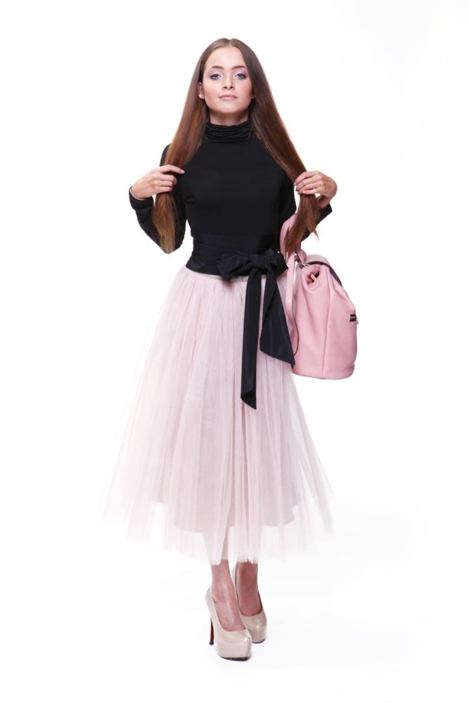 Юная леди стоит в розовой юбке с розовой сумкой