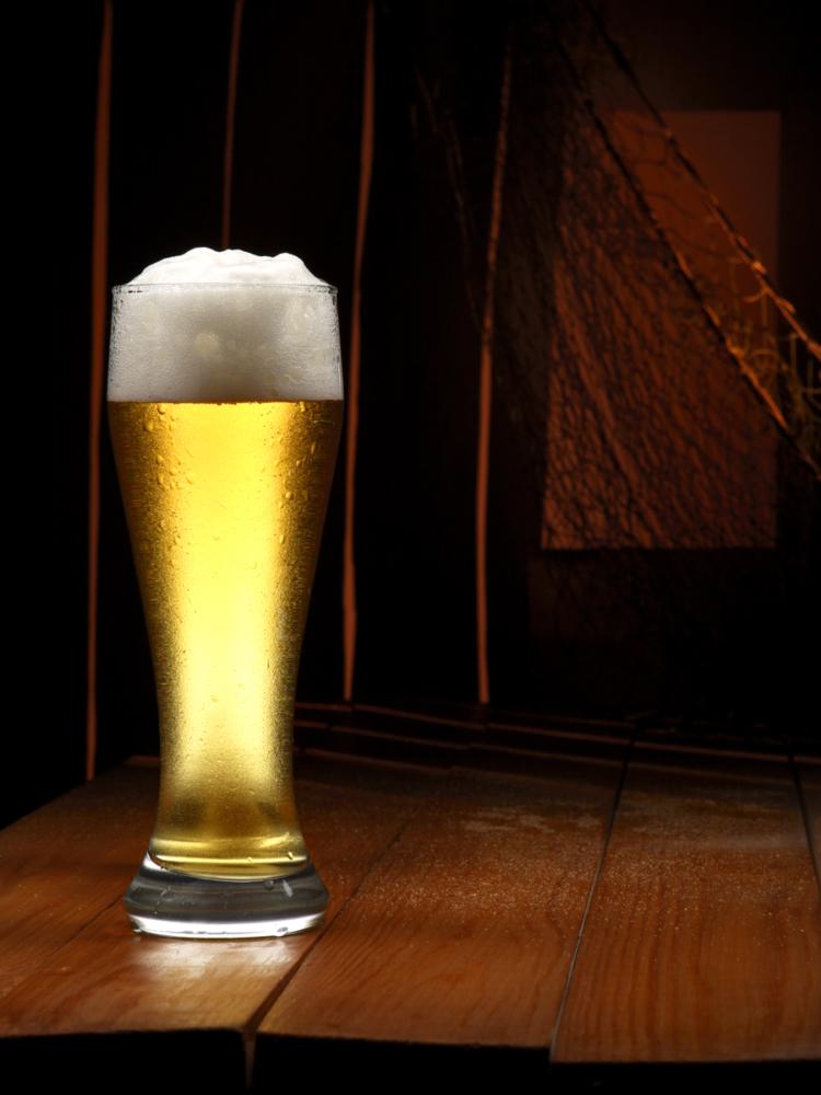 Бокал холодного пива с пеной на закате дня в хижине рыбака