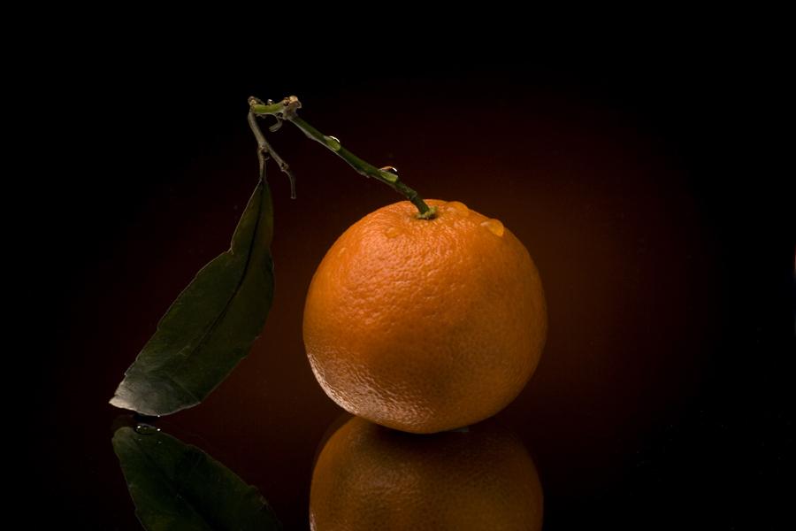 спелый мандарин с зелёным листочком