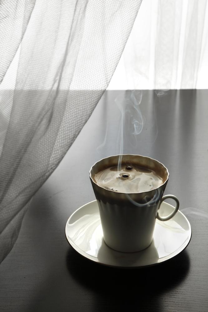 Горячий утренний кофе с дымком на столе у окна