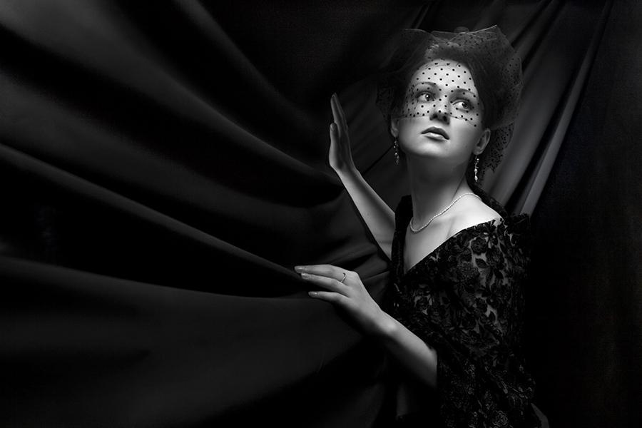 Молодая девушка в чёрном кружевном платье и вуалью на лице
