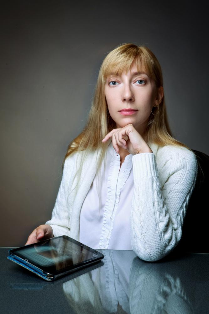 бизнес портрет молодой девушки сидячей за столом