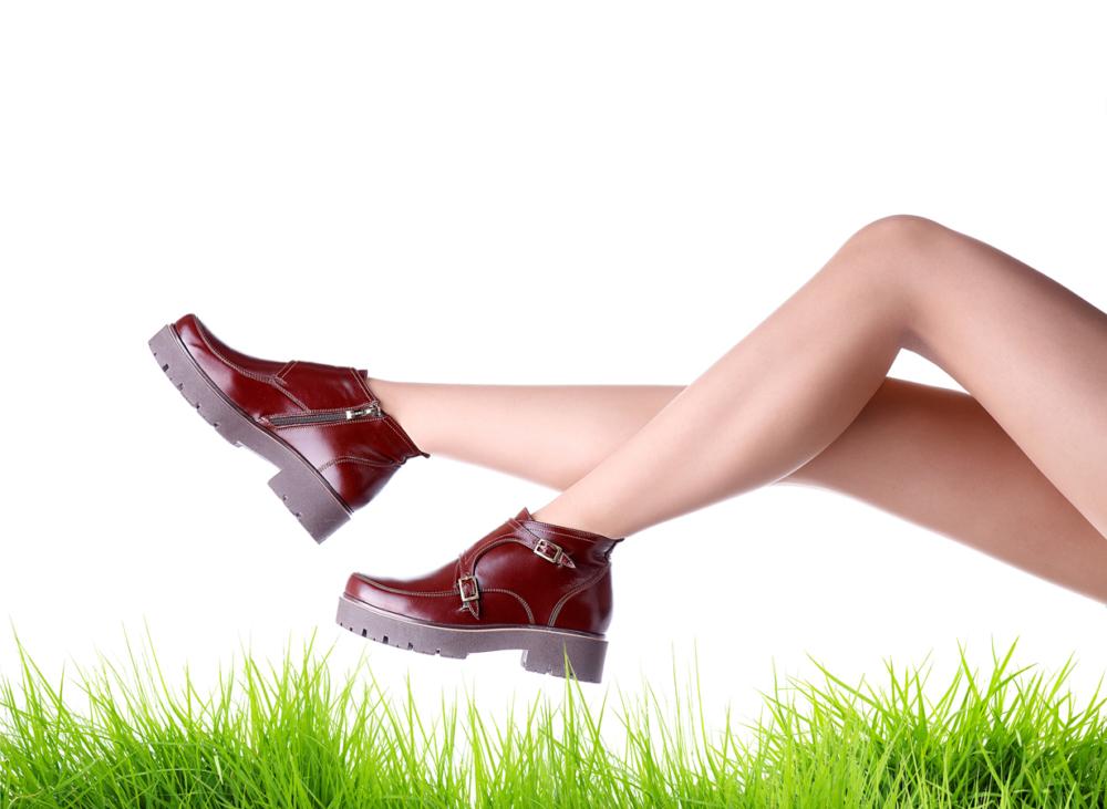 Красивые женские ножки в элегантных сапожках на травке